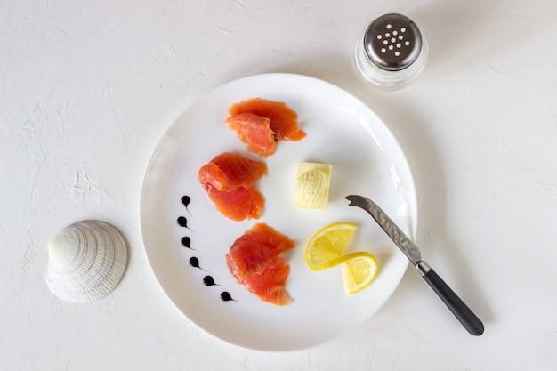 Trota, burro e limone su un piatto. sfondo bianco