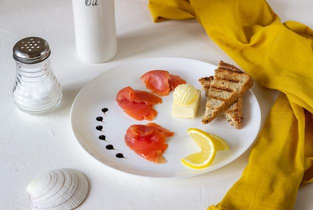 Trota, burro e pane su un piatto. sfondo bianco