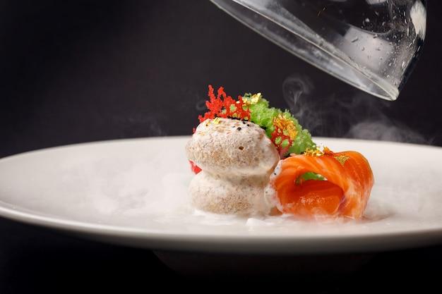 Trota gravlax di cucina molecolare con gelato all'aglio su uno sfondo nero