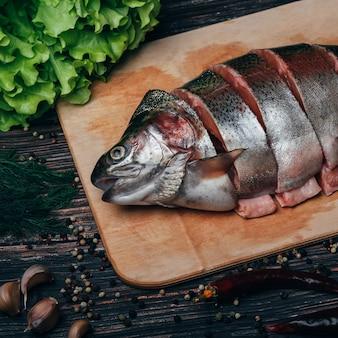 Trota tagliata a pezzi su una tavola di legno. pesce rosso fresco
