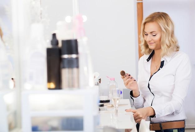 Truccatore che applica la cipria ad un cliente in un negozio di bellezza