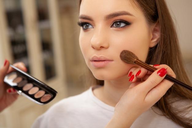Truccatore irriconoscibile che applica evidenziatore sulla pelle di una cliente femminile