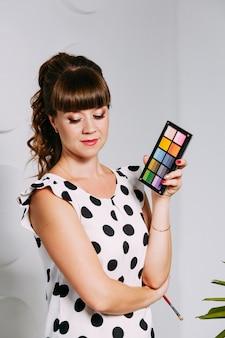 Truccatrice nel lavoro. ombre colorate in mano del truccatore. salone di trucco. concetto di trucco