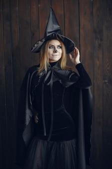 Trucco di halloween bella donna con acconciatura bionda. ragazza modello in costume nero. tema di halloween.