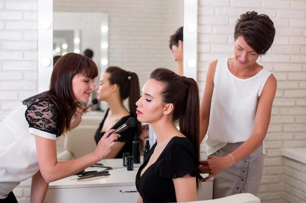 Trucco e acconciatura per bella donna castana nel salone di parrucchiere