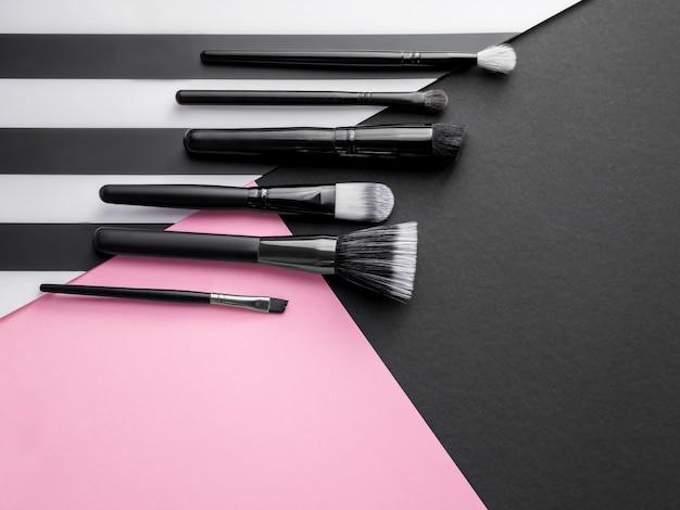 Trucco essenziale. set di pennelli trucco professionale su sfondo rosa e nero.