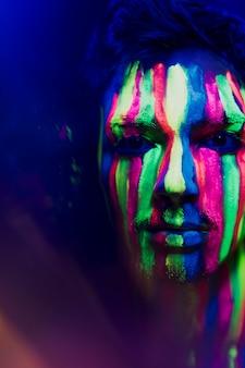 Trucco fluorescente colorato sul viso dell'uomo