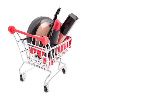 Trucco in carretto isolato su sfondo bianco. rossetto rosso, mascara, lucidalabbra rosa, polvere, smalto per unghie. prodotti di bellezza nel carrello, in sconti o in tema di vendita. must have e favoriti di bellezza
