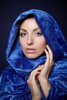 Trucco luminoso del bello ritratto del primo piano della donna in panno blu di colore isolato su oscurità
