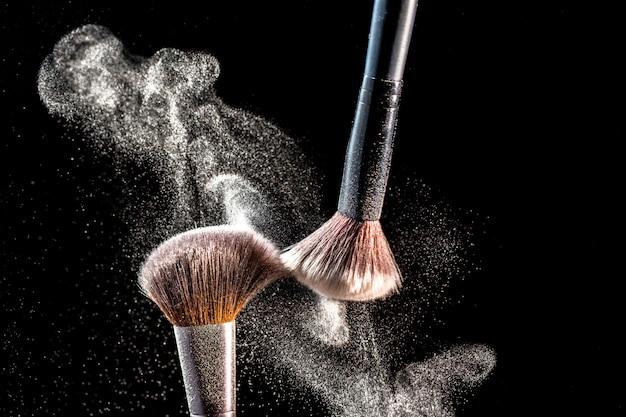 Trucco pennelli cosmetici con esplosione di fard in polvere