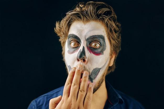 Trucco uomo del giorno della morte di halloween, sguardo sorpreso. sguardo scioccato e una mano sulla bocca. copia spazio