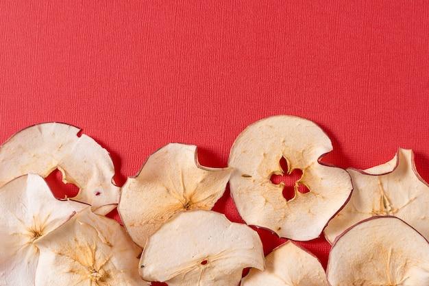 Trucioli di mele secchi su sfondo rosso con spazio di copia.
