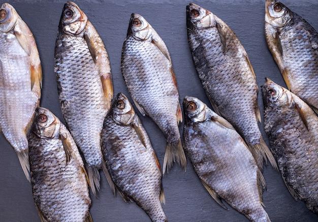 Truffa di pesce essiccato con squame su sfondo nero