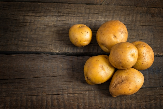 Tuberi di patata fresca sul vecchio tavolo di legno.