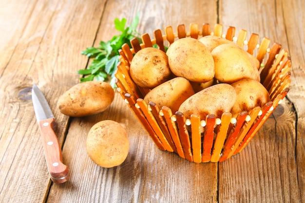 Tuberi di patata gialla su un vecchio tavolo di legno.