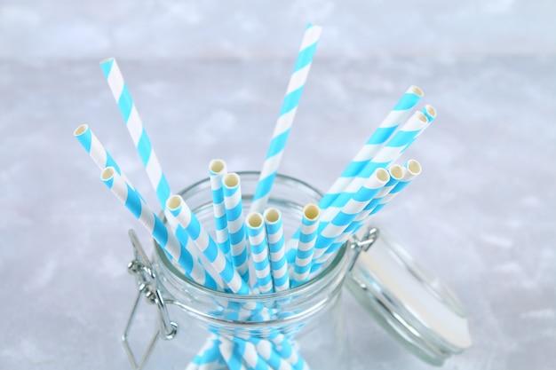 Tubi a gettare di carta a strisce blu in un vaso su un fondo grigio