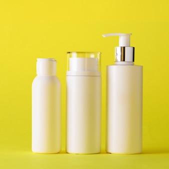 Tubi cosmetici bianchi su sfondo giallo con spazio di copia.