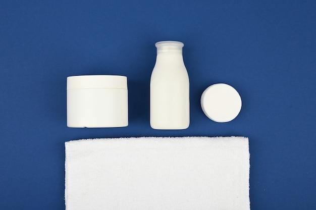 Tubi cosmetici vuoti bianchi su uno spazio blu del 2020. concetto di cura della pelle. con spazio di copia. l'appartamento stava mentendo. . dermatologia, primo piano.