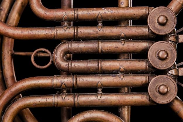 Tubi di bronzo vintage, valvola, elementi meccanici chiave corno francese su sfondo nero isolato.
