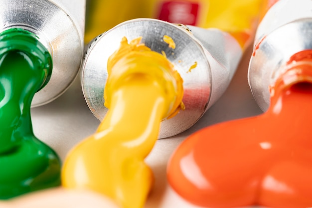 Tubi di vernice arancione, gialla e verde