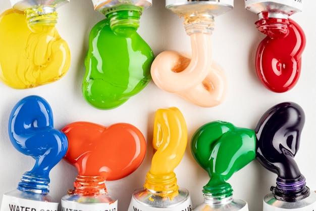 Tubi di vernice colorata sul tavolo bianco