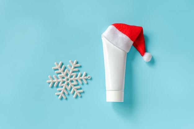 Tubo bianco cosmetico e medico per crema, unguento o altro prodotto in cappello rosso del babbo natale e fiocco di neve bianco sull'azzurro