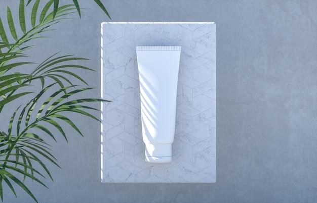 Tubo cosmetico su un podio di cemento con foglie di palma
