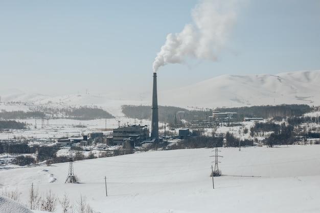 Tubo di fabbrica che inquina l'aria contro il tramonto, i problemi ambientali, il fumo dai camini
