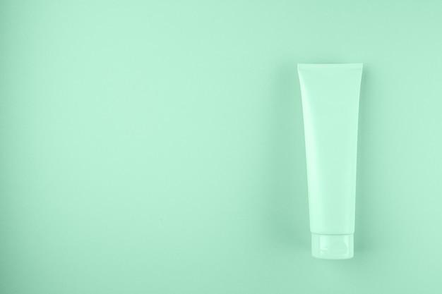 Tubo di plastica con crema viso o corpo color menta.