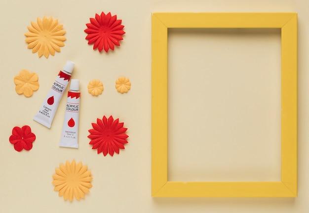 Tubo di vernice; ritaglio di fiore e bordo cornice in legno giallo su sfondo beige