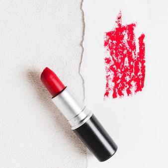 Tubo rosso del rossetto aperto e macchia sul foglio di carta