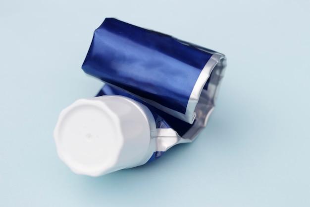 Tubo vuoto di dentifricio su sfondo blu