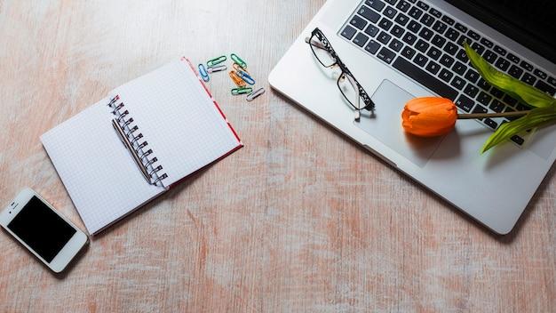 Tulip ed occhiali sul computer portatile con le cancellerie sul contesto di legno