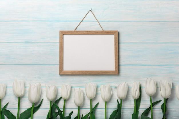 Tulipani bianchi e lavagna su tavole blu. festa della mamma