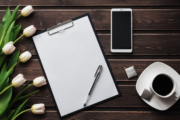 Tulipani bianchi su un tavolo di legno con una tavoletta di carta vuota e smartphone e una tazza di caffè