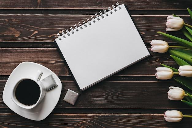 Tulipani bianchi su un tavolo di legno con una tazza di caffè e un taccuino vuoto