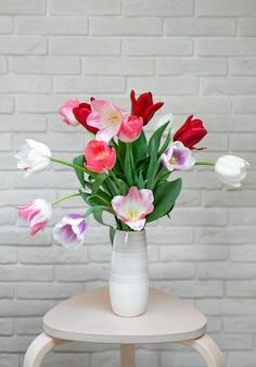 Tulipani colorati multi in un vaso in un interno moderno contro un muro di mattoni bianco.