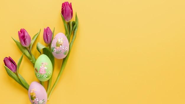 Tulipani con uova dipinte e copia-spazio