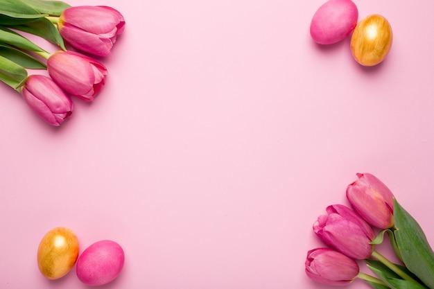 Tulipani delle uova di pasqua e dei fiori di rosa e dell'oro su una superficie rosa