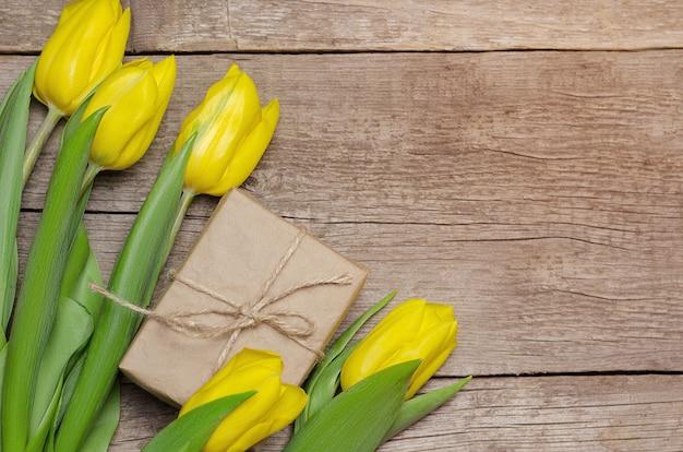 Tulipani e contenitore di regalo gialli su fondo di legno