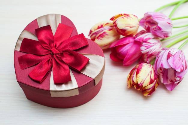 Tulipani e forma rosa della scatola del cuore isolati su bianco