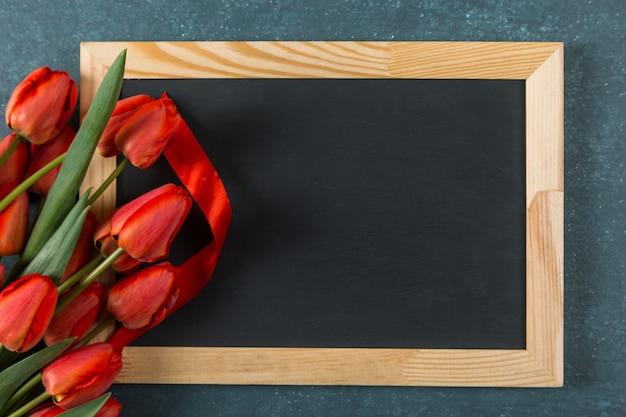 Tulipani e lavagna rossi sul blu, uno spazio in bianco per una cartolina per il giorno dell'insegnante. copia spazio.