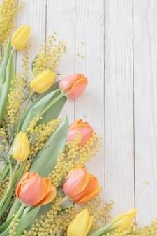Tulipani e mimose su fondo di legno bianco