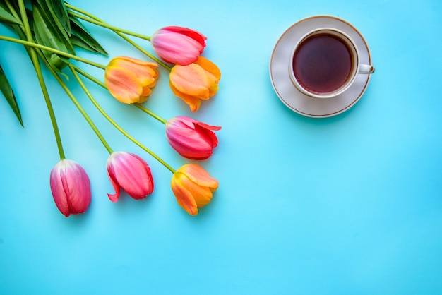 Tulipani e una tazza di tè o caffè su sfondo blu