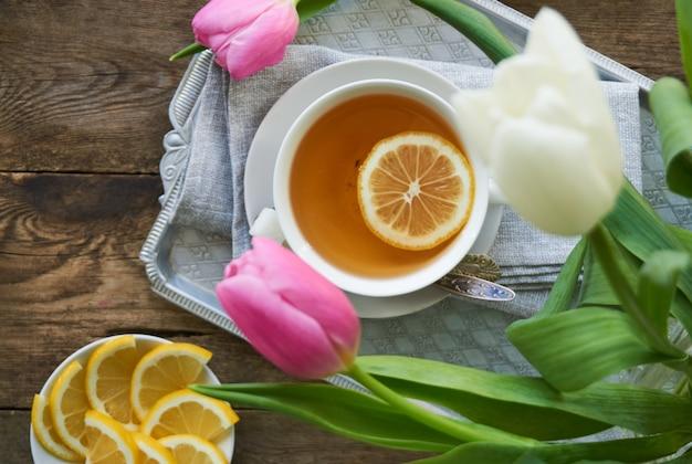 Tulipani e una tazza di tè verde al limone su un vassoio