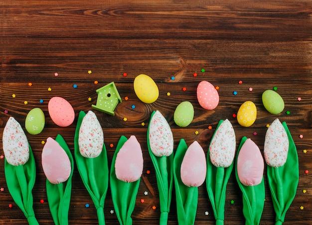 Tulipani fatti a mano e uova di pasqua su fondo in legno
