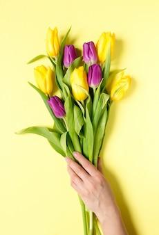 Tulipani fiori gialli e viola in un bouquet su uno sfondo giallo e le mani di una donna,