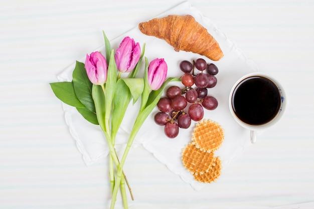 Tulipani freschi; croissant; uva; cialde e tazza di tè su sfondo bianco