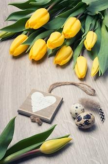 Tulipani gialli, cuore di legno e uova di quaglia sulla tavola di legno
