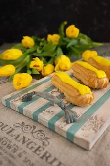 Tulipani gialli ed eclair sul vassoio in legno d'epoca